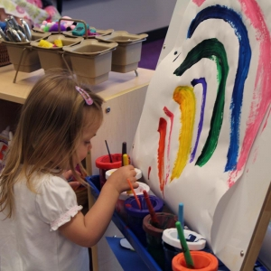 Under-five girl painting rainbow