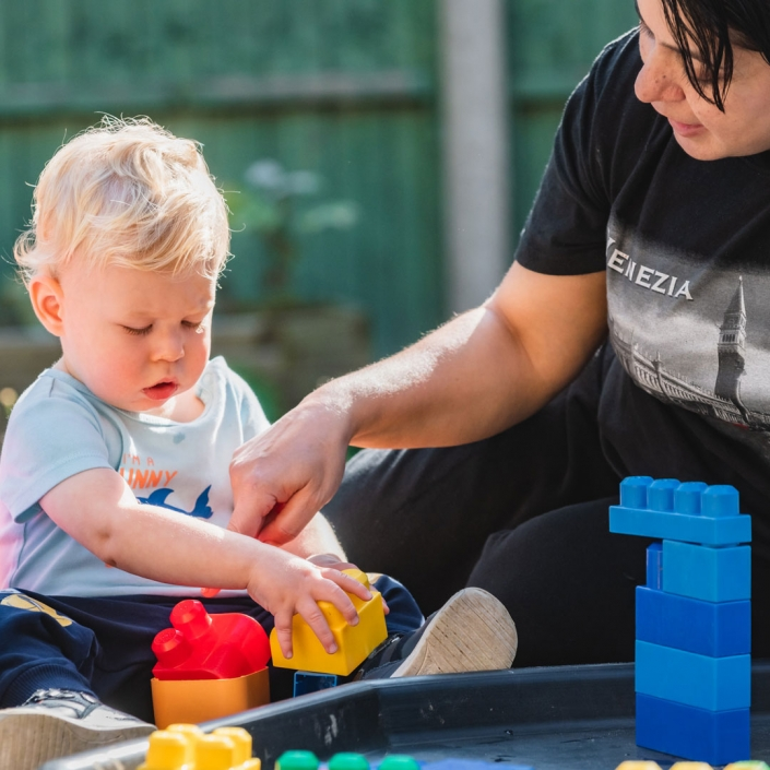 Photograph of a toddler playing & learning with staff at Little Cedars Day Nursery, Streatham.