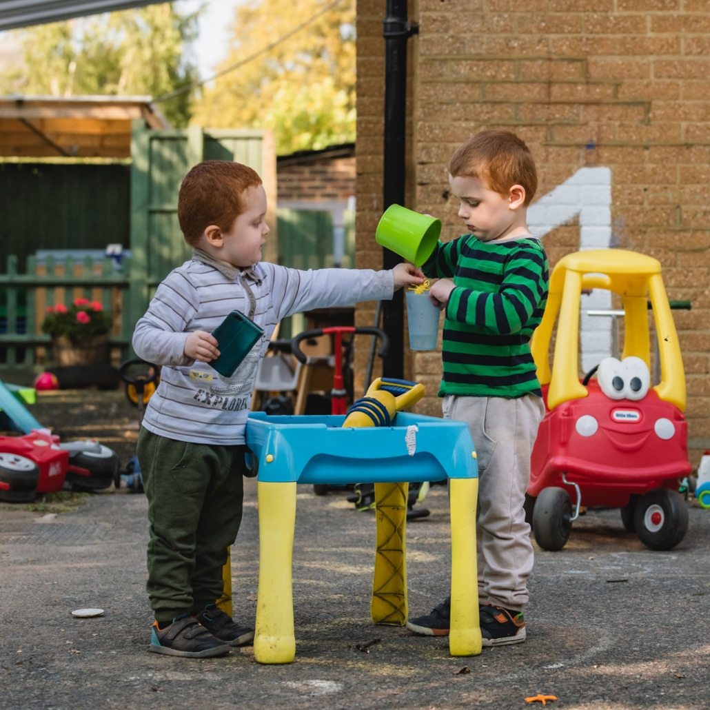 Image of two under-fives with some of the excellent outdoor equipment at Little Cedars nursery.