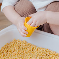 Child making a sound shaker with pasta shells